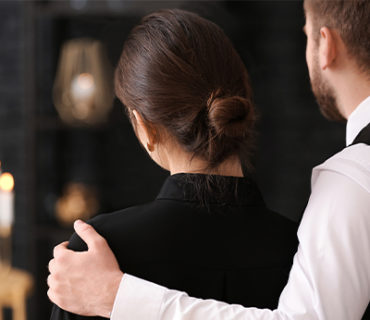 Man with his arm around a woman's shoulder