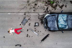woman lyind on the road after a car crash